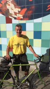 man posing with bicycle in front of mural