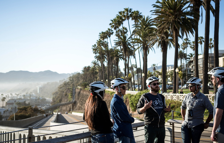Some tour goers and their guide talking in front of an iconic California sight