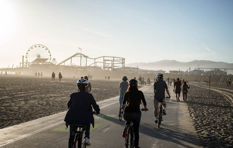 People biking through the bike lane close to the Santa Monica Pier
