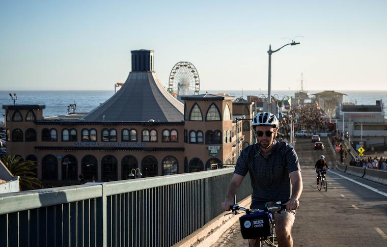 Guide biking through a lane with the Santa Monica Pier behind