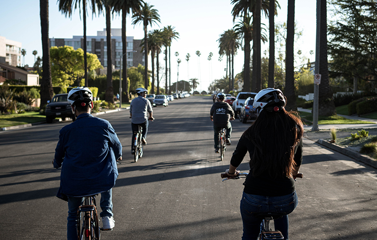 a group of people riding bicycles through hollywood boulevard