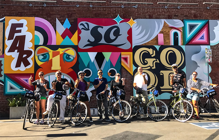 Group of tour goers and guide posing with their bikes and helmets in front of a mural