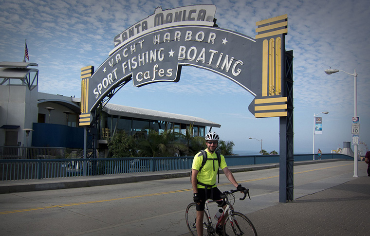 A tour goer in bike and helmet standing in front of a huge sign for the Santa Monica Yacht Harbor