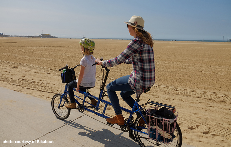 woman and child riding on a tandem bike
