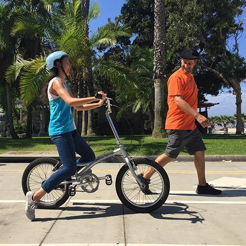 instructor teaching kid how to ride a bike