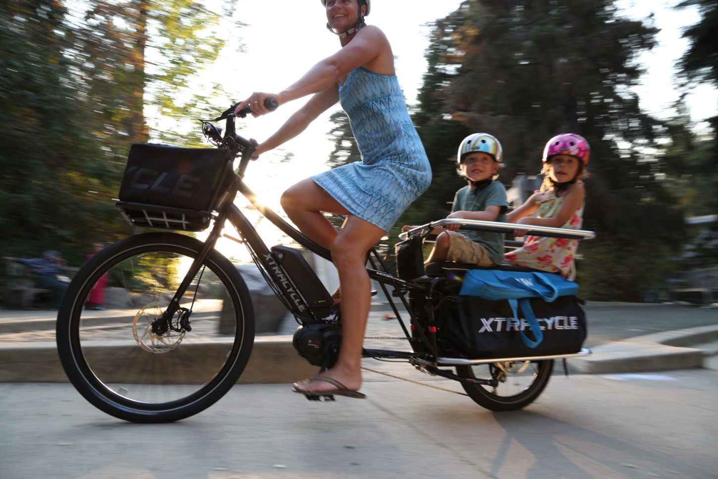 woman riding bike with children in the back cargo compartment