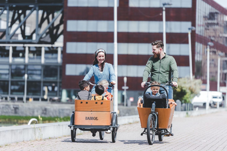 family riding babboe bikes through city