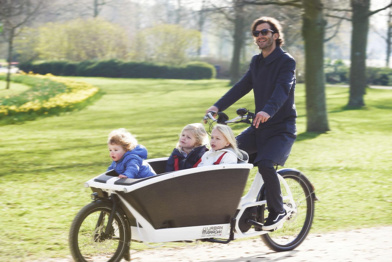 man riding urban arrow bicycle through a park with his kids