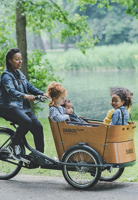 woman riding babboe bicycle with children in the front carriage