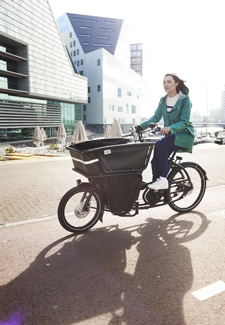 woman riding bicycle with cargo compartment in the front